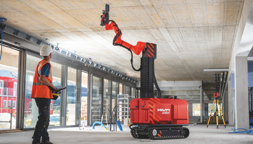 Construction worker safely operating ceiling drilling robot Jaibot on a jobsite